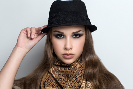 voyager: Young beautiful woman lady model woman actress. Bright stylish fashion look. Chic impressive appearance. Perfect face black makeup eyebrows smoky eyes arrows big lips. Hat traveler voyager world scarf Stock Photo
