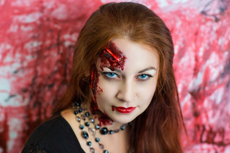sores: Pretty woman wound glass splinters in the skin, standing near bloody wall. Perfect idea for advertisement banner Halloween party card. Cosplay idea beauty monster, red sexy blood lips. Young face girl