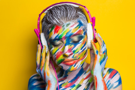 rythm: Person in headphones listening songs. Painted face bright art make up bodyart faceart, lady young beautiful girl. Colorful music equalizer photo bright background. World of rythm & melody party time