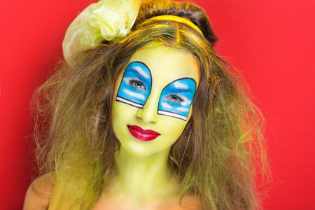 expressionism: Portrait of beautiful young girl (woman lady model) painting, art expressionism, realistic windows on yellow body wall. Bright creative makeup, expressive eyes, paint, colorful blue, red composition Stock Photo