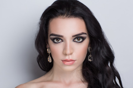puta: Perfect smoky eyes, professional make-up. Horizontal photo, free grey space for text. Portrait of black-haired girl with thick curly hair, best model agency, makeup studio visage master. fashion trend