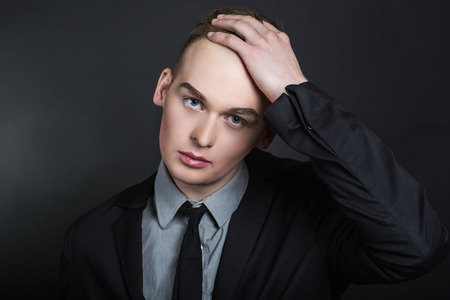 hair do: Bold man holds his hand on the top of his forehead. Problems with hair. Do not grow hair on the head, hair loss alopecia dandruff treatment of hair roots with a special shampoo and medical balsam.