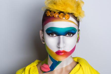 Surrealistisch schilderij op het gezicht van mooie jonge meid. De wereld van de fantasie, illusies, hallucinaties. De kunstenaar creëerde een nieuwe geometrische wereld, conceptuele kunst, professionele foto. Bright faceart