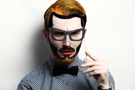 cheekbones: Young beautiful man. Bright creative make-up, style of comics. Red lips,black mustache, cheekbones .Yellow hair, beard. Stylish bow-tie, eyeglasses,watch. Creative idea is good for a poster. Stock Photo