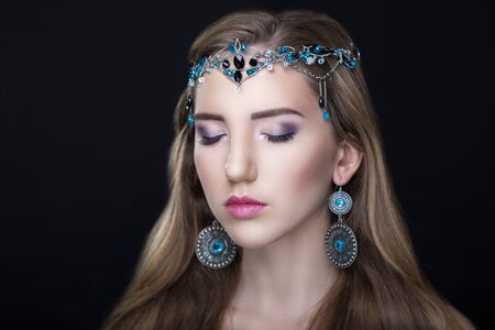 light hair: Beauty with large oriental ornaments jewelry silver circle earrings, tiara with blue black stones. Long light hair, beige skin, professional make up, shadows eyebrows pink sexy lips. Horizontal photo Stock Photo
