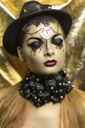 bodyart: Magic golden girl with bright makeup. Streams of gold, shiny tears drops on the cheeks, black steam punk hat, big collar, body art. Pink lips, chins, decorations, accessories. Professional photo, idea Stock Photo