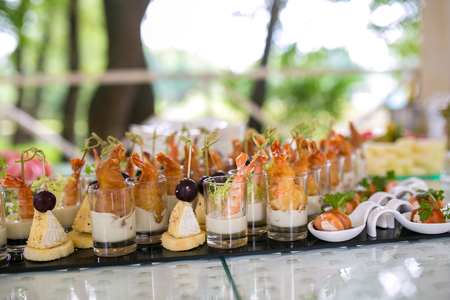 rich people: Tasty food, decorated shrimp in glass, green salad, fresh vegetables. Luxury table setting for banquets, party or wedding. Expensive service for rich people. Dishes for cafe, restaurant, bar or hotel. Stock Photo