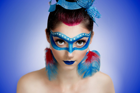 fantasy makeup: Young beautiful woman lady model woman character butterfly bird firebird ice queen. Creative perfect fantasy makeup. Bright saturated colors red blue mask eyes. Fairytale, stylish look. Stock Photo