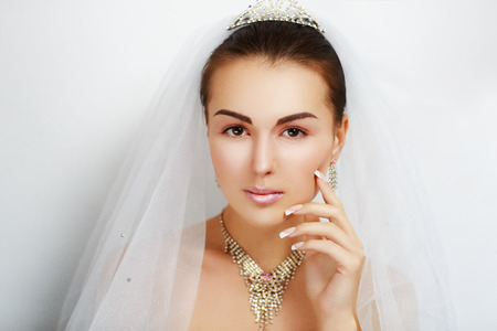 french manicure sexy woman: Charming girl with an angelic face and a beautiful bride accessories jewelry, crown, veil. Pretty young lady, smiley pink sexy lips, perfect shape brown eyebrows, big eyes, nude make up skin texture