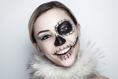 skull mask: Day of the Dead, Skull Mask. Art woman beautiful face painted as a traditional day of dead, white fur. Free place on photo for congratulations. Good for Halloween card, present, banner, advertisement Stock Photo
