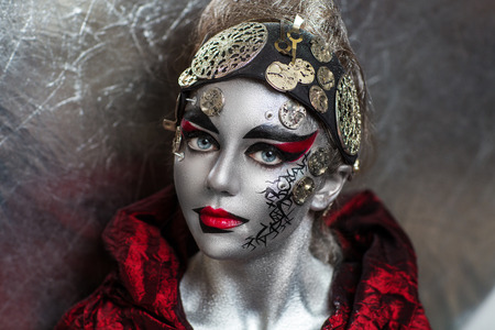 hitman: Portrait of beautiful young girl woman lady hitman killer techno future progress. Ideal creative expressive makeup silver skin face. Stylish bright showy look. Cosmo alien for banner Halloween party Stock Photo