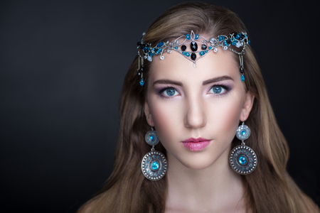silver circle: Beauty with large oriental ornaments jewelry silver circle earrings, tiara with blue black stones. Long light hair, beige skin, professional make up, shadows eyebrows pink sexy lips. Horizontal photo Stock Photo