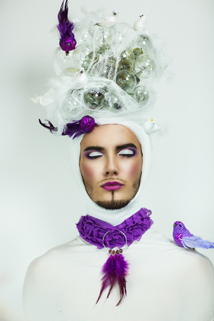 fashion art: Close-up portrait of perfect makeup man face. Bright colors - intensive lips, pink white shadows, long lashes. Creative dress with white purple birds sitting on head pigeon mail. New crazy art fashion Stock Photo