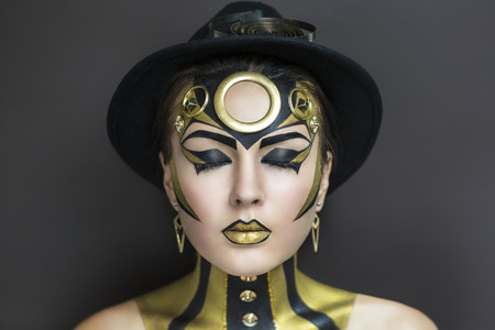 bodypaint: Techno golden girl with bright makeup. Streams of gold, shiny cheeks, black steam punk hat, big circle on forehead, body art. Sexy lips, decorations, accessories. Professional photo, new stylish idea