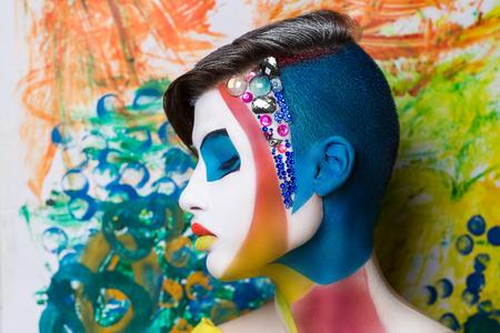 Surrealistisch schilderij op het gezicht van mooie jonge meid. De wereld van de fantasie illusies hallucinaties. De kunstenaar creëerde een nieuwe geometrische wereld, conceptuele kunst, professionele foto. Bright faceart Stockfoto