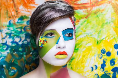 surrealistic: Surrealistic painting on the face of beautiful young girl. The world of fantasy illusions hallucinations. The artist created a new geometric world, conceptual art, professional photo. Bright faceart Stock Photo