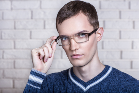 black rimmed: Successful man Portrait of perfect worker. Stylish short hair dress, white brick wall background, hands holding bow black rimmed eye glasses lense. Think new idea how to create new project development