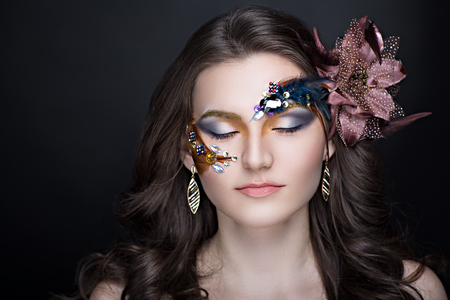 decorative accessories: Close-up portrait of perfect woman face. Bright make up - beige lips, orange blue shadows, long lashes. Long curly hair with decorative accessories made of fur feathers. New crazy art idea conceptual
