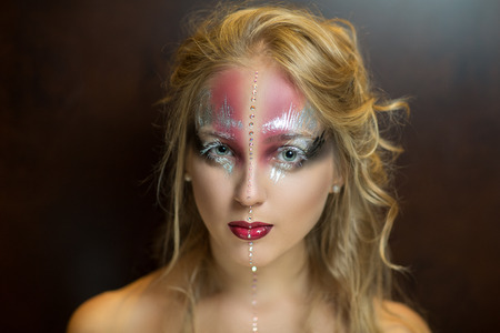 fantasy makeup: Young beautiful woman, pretty lady, beauty fashion model, perfect woman, fairy-tale character, silver & pink butterfly, ice queen. Creative fantasy makeup. Bright, saturated colors mask, stylish eyes