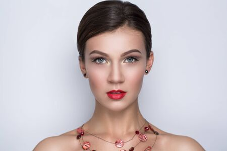 Portrait close-up of very beautiful perfect woman with bright make up, red velvet lipstick, necked shoulders pretty face, stylish hair do, smoky eyes Clean white wall photo studio background for text. Stock Photo