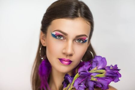 ear rings: Beautiful woman portrait face, bright pink blue make up, big eyes, new cosmetics shiny glossy lips, colorful flowers art spring blossom, beauty fashion style close up. jewelry ear rings long feathers Stock Photo