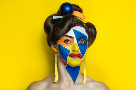 hallucinations: Colorful painting on the face of beautiful young girl. The world of fantasy, illusions, hallucinations. The artist created a new geometric world, conceptual art, professional photo. Bright faceart Stock Photo