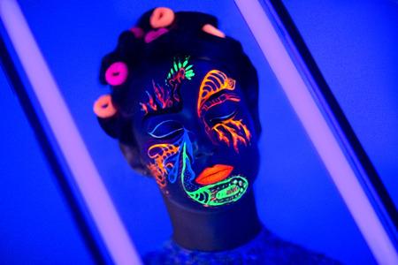 gogo girl: Gesicht der Frau mit fluoreszierenden bilden Kunst. Blauer Hintergrund. Studio gedreht. Orange, gr�n, rosa Neon Farben. Kreative Idee ist gut f�r die Clubs, Disco, Go-Go, Show Konzerte, Partys. Sexy girl alien cosmo