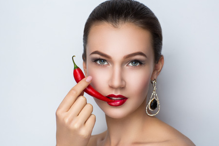 Young beautiful brunette woman (lady model woman actress). Luxury bright stylish look. Chic impressive appearance. Perfect face smoky eyes makeup brown eyebrows arrows red lips. Long red chili peper