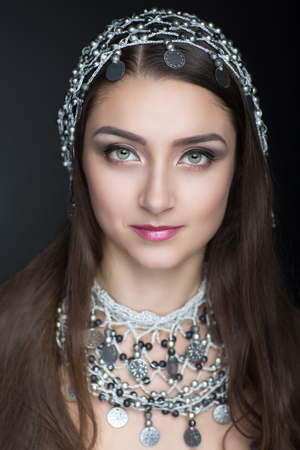 dark brown hair: Beauty with new oriental ornaments jewelry silver circle coins, tiara hat cap with shiny stones. Long dark brown hair, beige skin, professional make up, shadows eyebrows pink sexy lips. Vertical photo