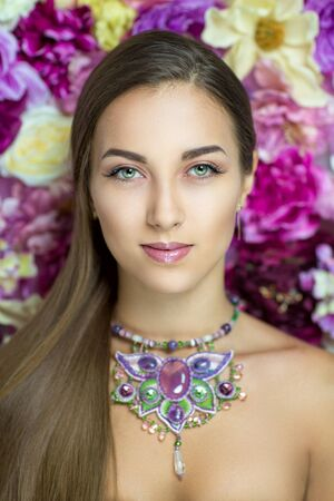 floristry: Beautiful woman portrait face, bright yellow purple floristry, big eyes, new cosmetics, shiny glossy lips, colorful flowers, art spring blossom, beauty fashion style close up. Big jewelry necklace