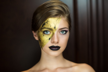 Creative golden girl with bright makeup. Streams of gold, shiny cheek, colored part of face, black lips Stock Photo - 57660476