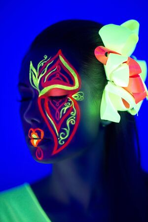 Woman's face with fluorescent make up art. Banque d'images