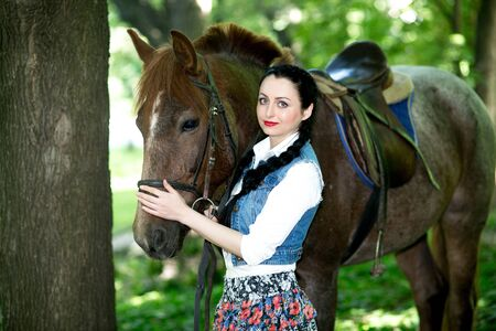 fairy  tail: Beautiful girl near brown horse, pinto with a spot. Forest, bright light, professional photo. Looks like film or fairy tail, cosplay. white blouse, denim jacket, black hair braided, skirt floral print