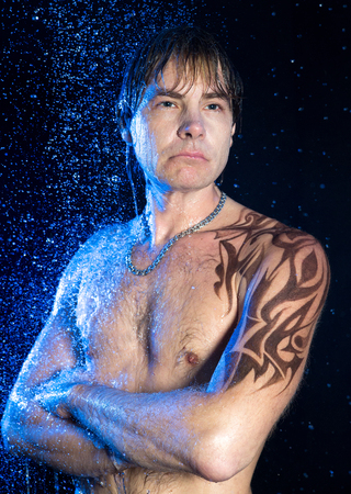 man power: Close-up portrait of handsome man with graphic brown water-resistant tattoo on shoulder and neck, strong arms crossed on his chest.