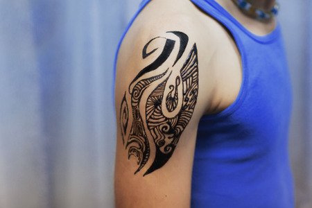 color tribal tattoo: Indian tattoo on mans shoulder