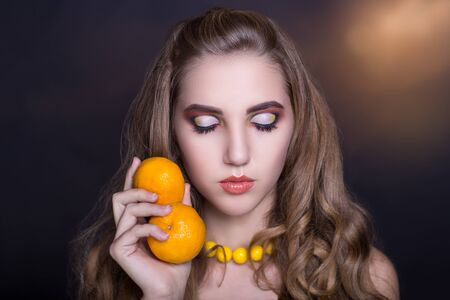 going for it: girl with bright colored makeup, beauty portrait person. A woman is holding tasty orange in her hand and is going to eat it. new art idea, conceptual professional photo. ready for new year party time