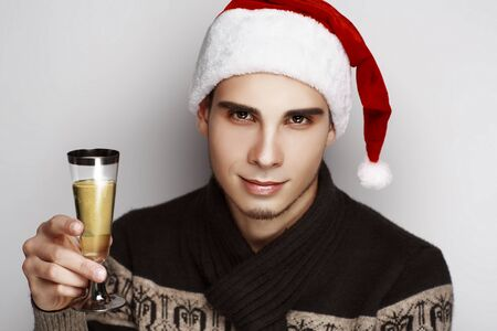 Young handsome guy man model santa claus. light grey background New Year Christmas holiday vacation. Stylish look cap, sweater scarf accessories. Hand holding a transparent glass of champagne bubbles