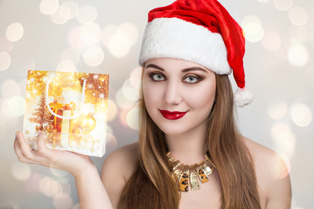 night before christmas: Beautiful woman Santa Claus holding on hand golden beg with presents, make a wish before Christmas and New Year night. Prepare to bright winter holiday. Red white hat cap with bubo and fur. Red lips