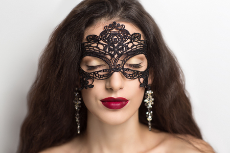 role play: Close up portrait of Beautiful girl lady woman in a black lace mask. A mysterious stranger sexy role play. Closed eyes professional make up red lips brown golden shadows black arrows. Stylish picture Stock Photo