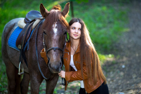 fairy  tail: Professional photo of young beautiful girl, brown horse, pinto with a spot. Forest, bright light, green grass. Looks like film, fairy tail, cosplay. white blouse, jacket, long hair. Touch animals nose Stock Photo