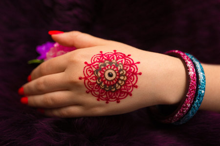 resistant: Indian picture on hands palm, mehendi tradition decoration, resistant design by special paint, brown, red, pink henna round mandala. Long nails new shape manicure. Saloon service art style, jewelry