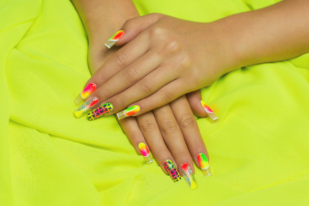 french manicure sexy woman: Two female hands on a bright fabric, neat manicure with creative nails different colors. fluorescent art. Bright lemon background. Studio shot. Orange, green yellow neon paints. idea is good for disco