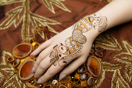 resistant: Indian picture on hands palms, mehendi tradition decoration, resistant design by special paint swan, brown, orange henna heart swans love. Long nails new shape manicure. Saloon service style, jewelry