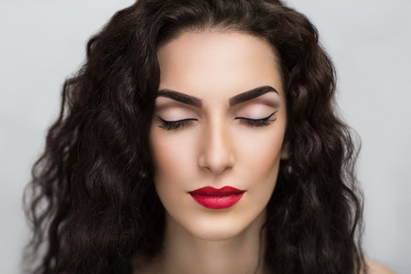 Portrait of beautiful young girl, woman, lady, model. Flawless makeup, perfect shape of the eyebrows, long eyelashes, bright red lipstick. Image can be used for advertising of cosmetic products. Banque d'images