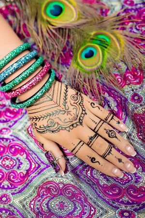 lacquer: Womens beautiful hand with delicate fingers and a neat white lacquer manicures, henna with decorative elements. Indian oriental style, ornamental patterns. Luxury bracelets, green peacock feathers