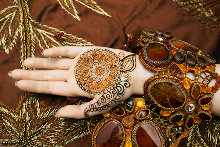resistant: Indian picture on hands palms, mehendi tradition decoration, resistant design by special paint swan, brown, orange henna round mandala. Long nails new shape manicure. Saloon service style, jewelry