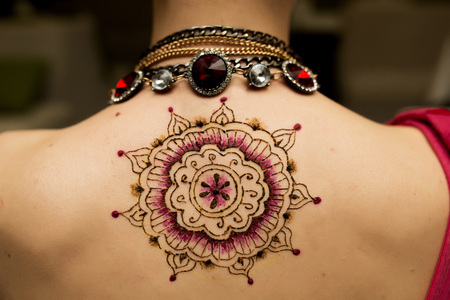 strass: Hennaed beautiful female back, round mandala image, traditional Indian, Pakistani, African, Oriental motifs, cultural traditions and customs. Mehendi made of brown, black red henna paste. Professional Stock Photo