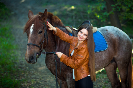 long nose: Professional photo of young beautiful girl, brown horse, pinto with a spot. Forest, bright light, green grass. Looks like film, fairy tail, cosplay. white blouse, jacket, long hair. Touch animals nose Stock Photo