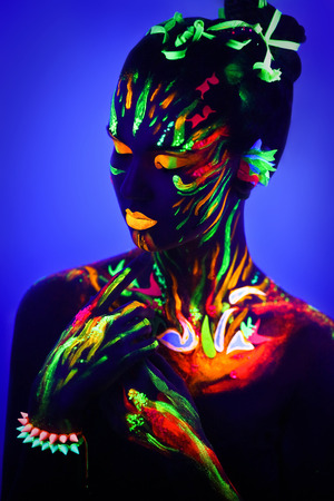 Woman's face with fluorescent make up art. Blue background. Studio shot. Orange, green, yellow neon paints. Creative idea is good for clubs, disco, go-go, show concerts, parties. Sexy girl alien cosmo 스톡 콘텐츠