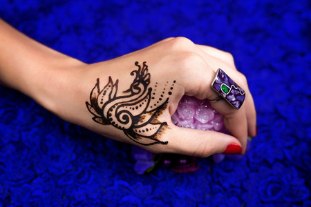 Indian picture on hands palm, mehendi tradition decoration, resistant design by special paint swan, brown, black henna art love. Long red nails new shape manicure. Saloon service style, jewelry, ring
